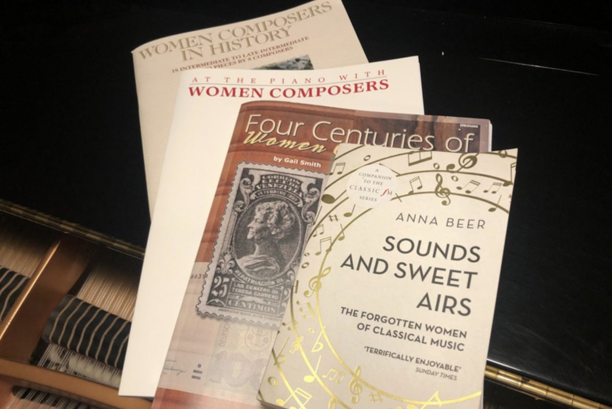 Three sheet music anthologies of female composers (published by Hal Leonard, Alfred, and Mel Bay) and the book Sounds And Sweet Airs by Anna Beer on top of a piano