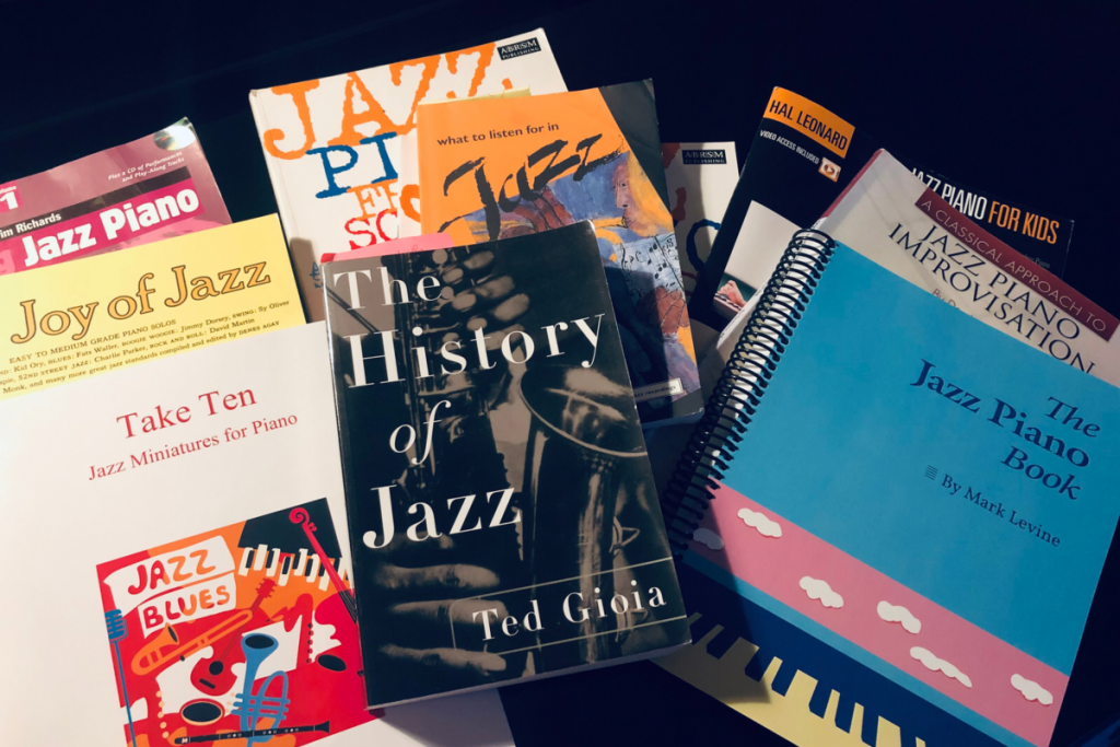 A photo of all the resources and books mentioned in this article on top of a piano